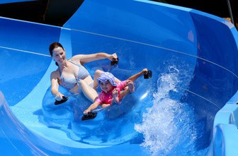 Young mother and child (girl age 04)  having fun in water park. Concept photo with copy space